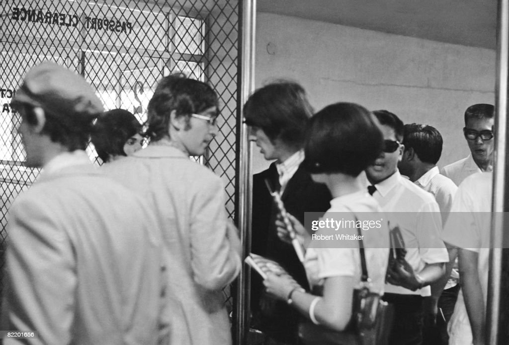 John Lennon (1940 - 1980, centre, left) and George Harrison (1943 - 2001, centre, right) at Manila International Airport after the Philippines leg of the Beatles' final world tour, 5th July 1966. The group made a hasty exit from the country after a perceived snub on President Ferdinand Marcos and his wife Imelda resulted in official hostility, including the withdrawal of police protection for the group.