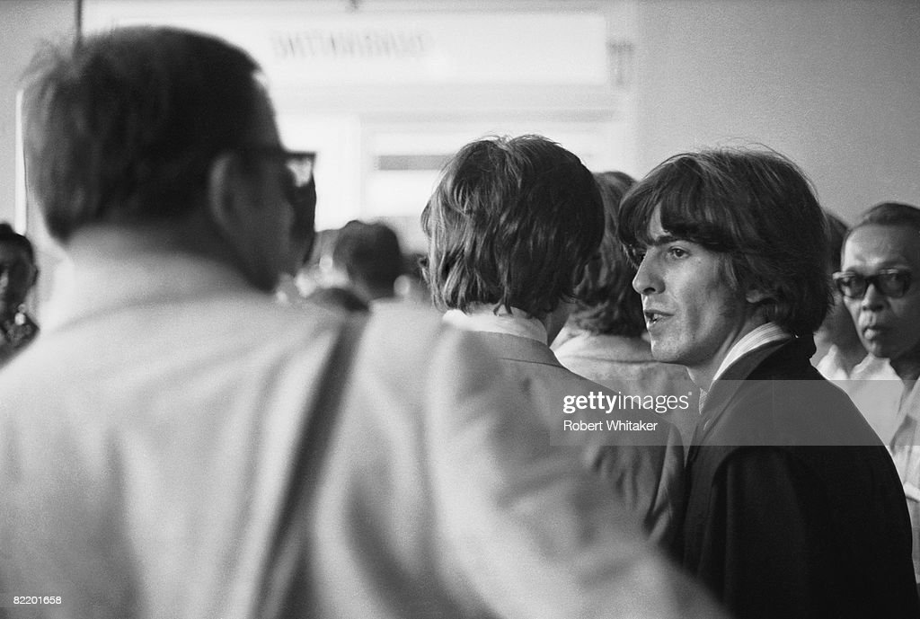 John Lennon (1940 - 1980, centre) and George Harrison (1943 - 2001, right) at Manila International Airport after the Philippines leg of the Beatles' final world tour, 5th July 1966. The group made a hasty exit from the country after a perceived snub on President Ferdinand Marcos and his wife Imelda resulted in official hostility, including the withdrawal of police protection for the group.