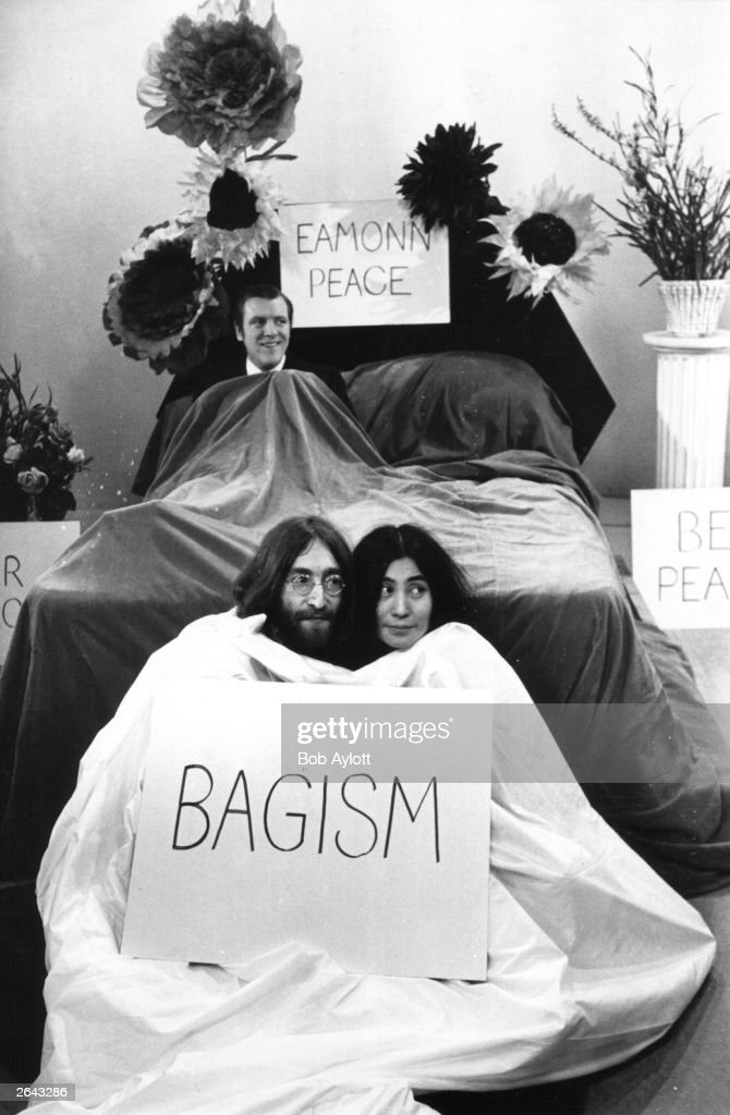 John Lennon (1940 - 1980) and his wife, Japanese born artist Yoko Ono, sit in a bag before appearing on the 'Today' programme with Eamonn Andrews (1922 - 1987), seen in bed in the background.