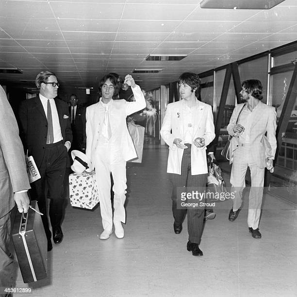 John Lennon and Paul McCartney of The Beatles arriving at London Airport 16th May 1968 They are both dressed in white and carrying apples to promote...