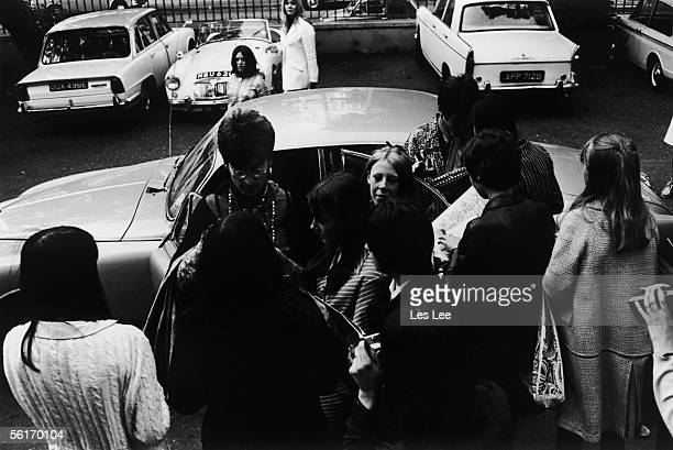 John Lennon and Paul McCartney signing autographs for fans as they arrive at EMI studios Abbey Road for a rehearsal with the Beatles during the...