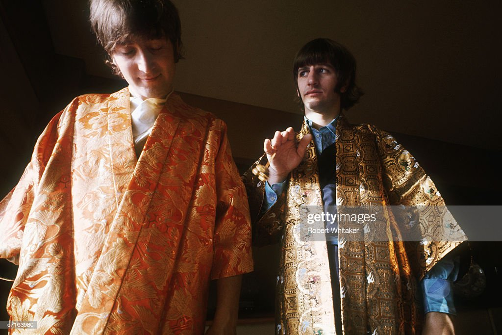 John Lennon (1940 - 1980) and Ringo Starr try on a pair of gold embroidered kimonos in Tokyo during the Beatles' Asian tour, 1966.