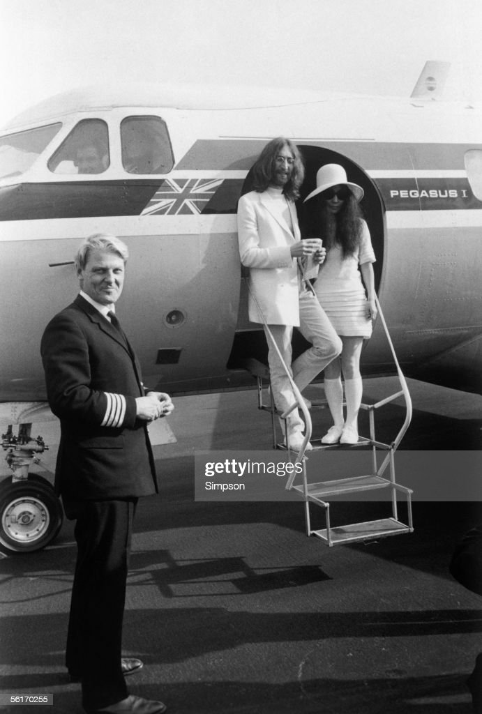 John Lennon and Yoko Ono, both dressed in white, board a private aircraft in Gibraltar after their wedding, 20th March 1969. Their pilot Trevor Copleston stands by the plane.