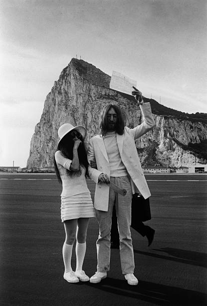 John Lennon and Yoko Ono, both dressed in white, with...
