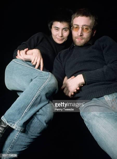 John Lennon and Yoko Ono dressed alike lie down for a portrait together