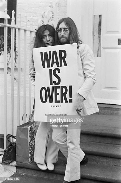 John Lennon and Yoko Ono pose on the steps of the Apple building in London, holding one of the posters that they distributed to the world's major...