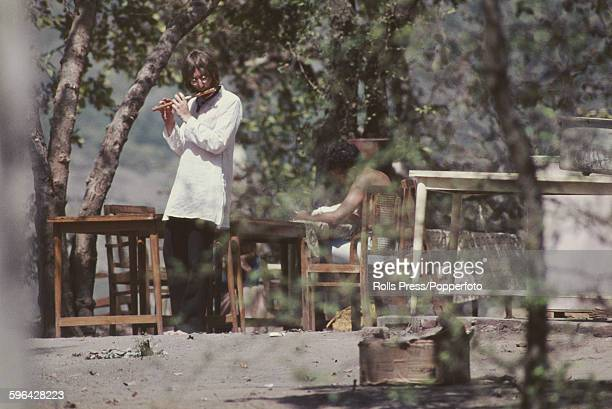John Lennon from The Beatles pictured playing a flute as he walks barefoot through the Chaurasi Kutia ashram compound of Maharishi Mahesh Yogi near...