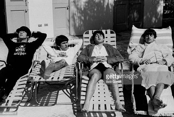 John Lennon George Harrison Paul McCartney Ringo Starr members of British rock group The Beatles relaxing on lounge chairs at poolside of the...