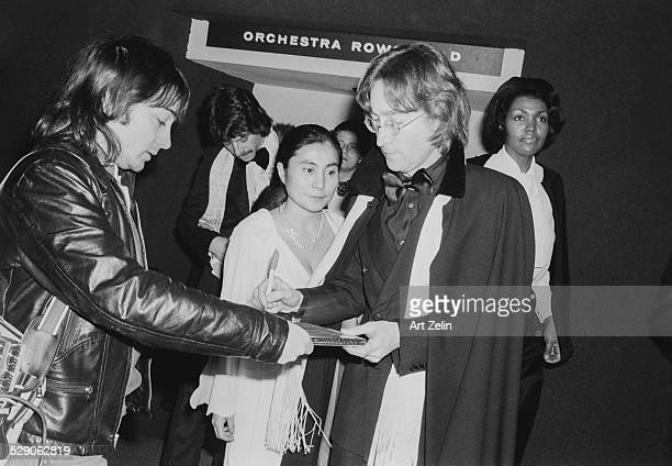 John Lennon giving autograph to hound who became photographer Vinny Zafonti circa 1960 New York Behind them is Japanese artist and musician Yoko Ono