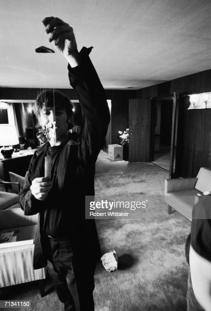 John Lennon holding up ornate wind chimes in the Beatles Tokyo Hilton Hotel suite Japan during their tour of Asia 1966