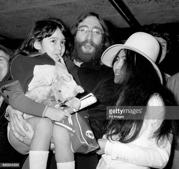 John Lennon holds Kyoko Cox the 6 year old daughter of his Japanese wife Yoko Ono on the child's arrival at Heathrow airport where she had flown in...