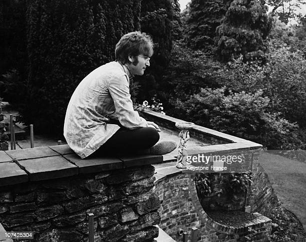 John Lennon In His Home Sitting On A Wall At Weybridge On England During Sixties