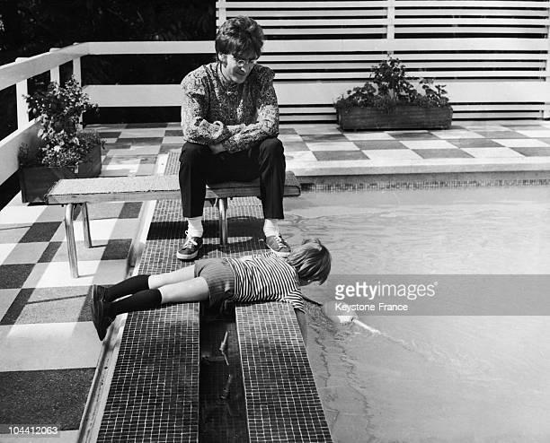 John LENNON is having fun watching his son Julian playing on the edge of the swimmingpool in their house in Weybridge Britain