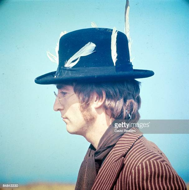 John Lennon of English rock and pop group The Beatles wearing a hat decorated with feathers takes part in filming of the television musical film...