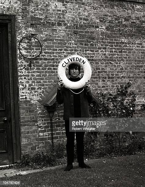 John Lennon of the Beatles framing his face with a lifebelt during a break in the filming of 'Help' at Cliveden House in Buckinghamshire May 1965