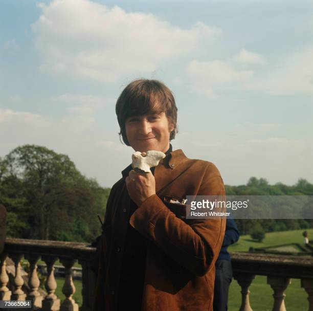 John Lennon of the Beatles holding up a stone during a break in the filming of 'Help' at Cliveden House in Buckinghamshire May 1965