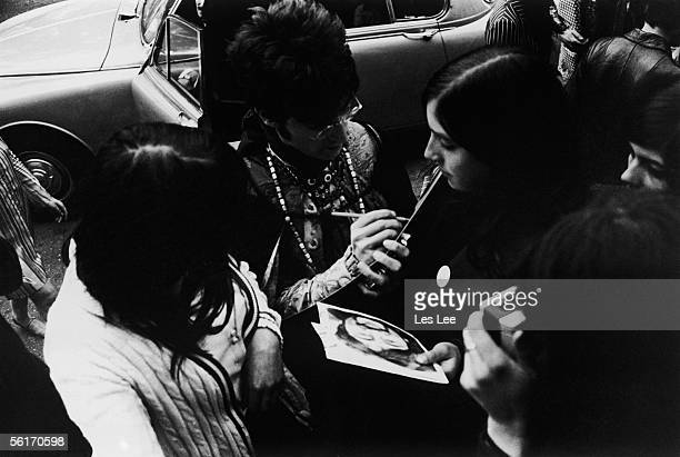 John Lennon of the Beatles signs autographs for fans as he arrives for rehearsals at the EMI studios in London 22nd June 1966