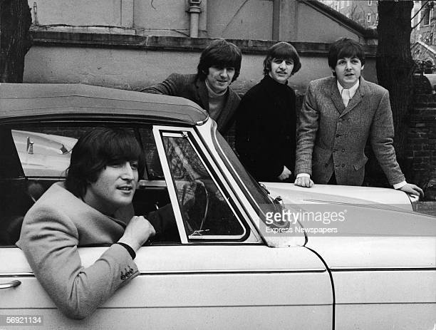 John Lennon of the British pop group the Beatles sits in his car after passing his driving test February 16 1965 Bandmates from left George Harrison...