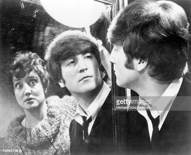 John Lennon of the rock and roll band 'The Beatles' in a still with an actress from their movie 'A Hard Day's Night' which was released on August 11...