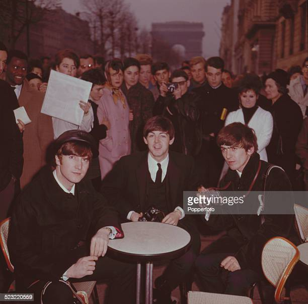John Lennon Paul McCartney and George Harrison from The Beatles posed sitting on café chairs on the Avenue des ChampsElysees in Paris France in...