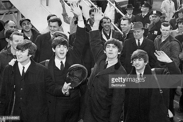 John Lennon Paul McCartney George Harrison and Ringo Starr wave to screaming Beatles fans as the Fab Four arrive at Kennedy Airport in Queens New York