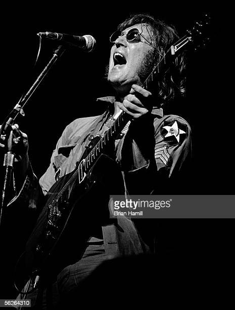 Britishborn singer and songwriter John Lennon dressed in a military jacket and sunglasses sings into a microphone as he performs onstage at the 'One...