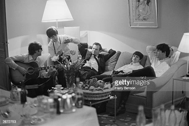 John Lennon plays his guitar while the other Beatles and manager Brian Epstein relax in a hotel room in Paris.