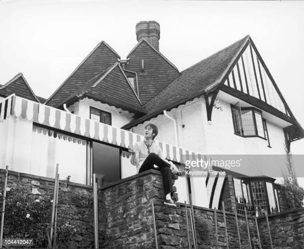 John LENNON posing in front of his house in Weybridge Surrey between 1966 and 1968 John LENNON who bought this house in 1964 sold it in 1968