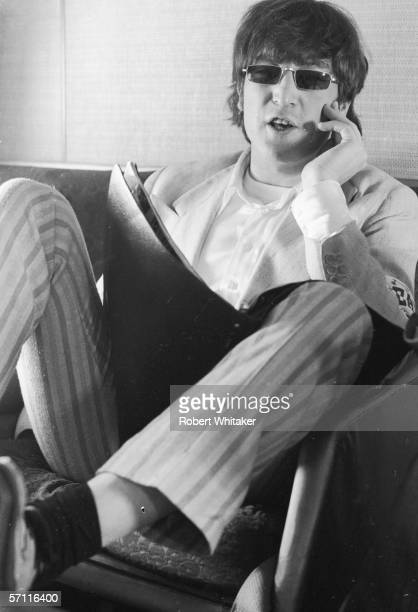 John Lennon relaxes aboard a chartered jet bound for Manila in the Philippines during the Beatles' Asian tour 3rd July 1966