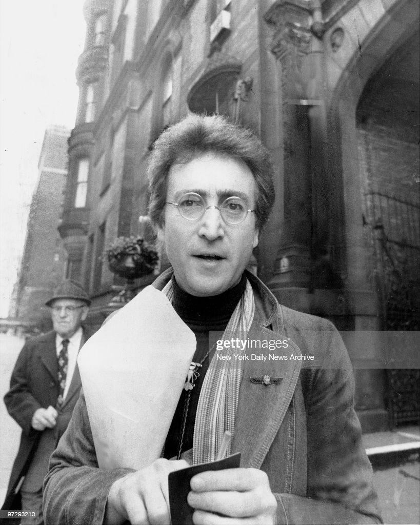 John Lennon returning from florist shop outside his apartment at the Dakota.,
