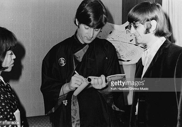 John Lennon signs an autograph with journalist Rumi Hoshika and Ringo Starr during a Beatles interview for Japanese music magazine 'Music Life' Tokyo...