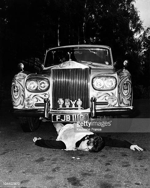John LENNON singer of the BEATLES acting like he was run over by his own car a ROLLS ROYCE covered with a psychedelic paint