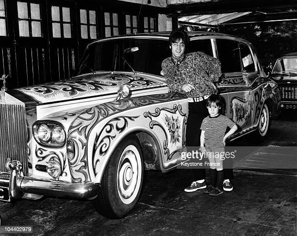 John LENNON the singer of the British pop group BEATLES posing with his son in his garage in front of his psychedelic car