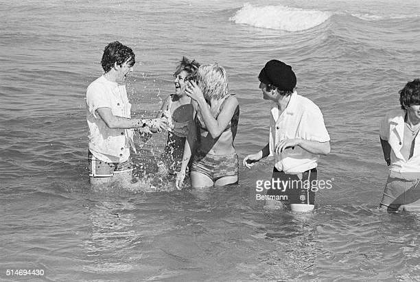 John Lennon watches as Paul McCartney splashes two girls while playing in the Atlantic Ocean Miami Beach Florida