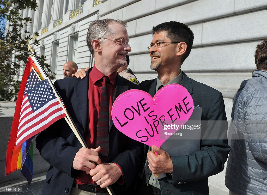 John Lewis, left, and his husband Stuart Gaffney, plaintiffs in the 2008 Defense of Marriage Act (DOMA) case, hold flags and a sign reading 'Love is Supreme' outside City Hall after the U.S. Supreme Court same-sex marriage ruling in San Francisco, California, U.S., on Friday, June 26, 2015. Same-sex couples have a constitutional right to marry nationwide, the U.S. Supreme Court said in a historic ruling that caps the biggest civil rights transformation in a half-century. Photographer: Josh Edelson/Bloomberg via Getty Images