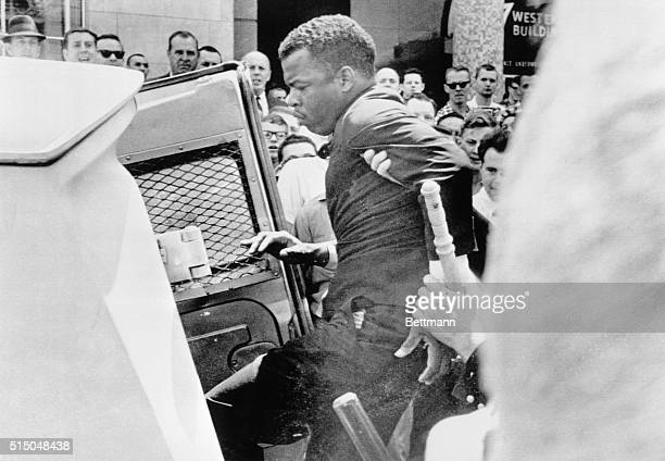 John Lewis national chairman of the Student Nonviolent Coordinating Committee is ushered into police patrol wagon during racial demonstration here...
