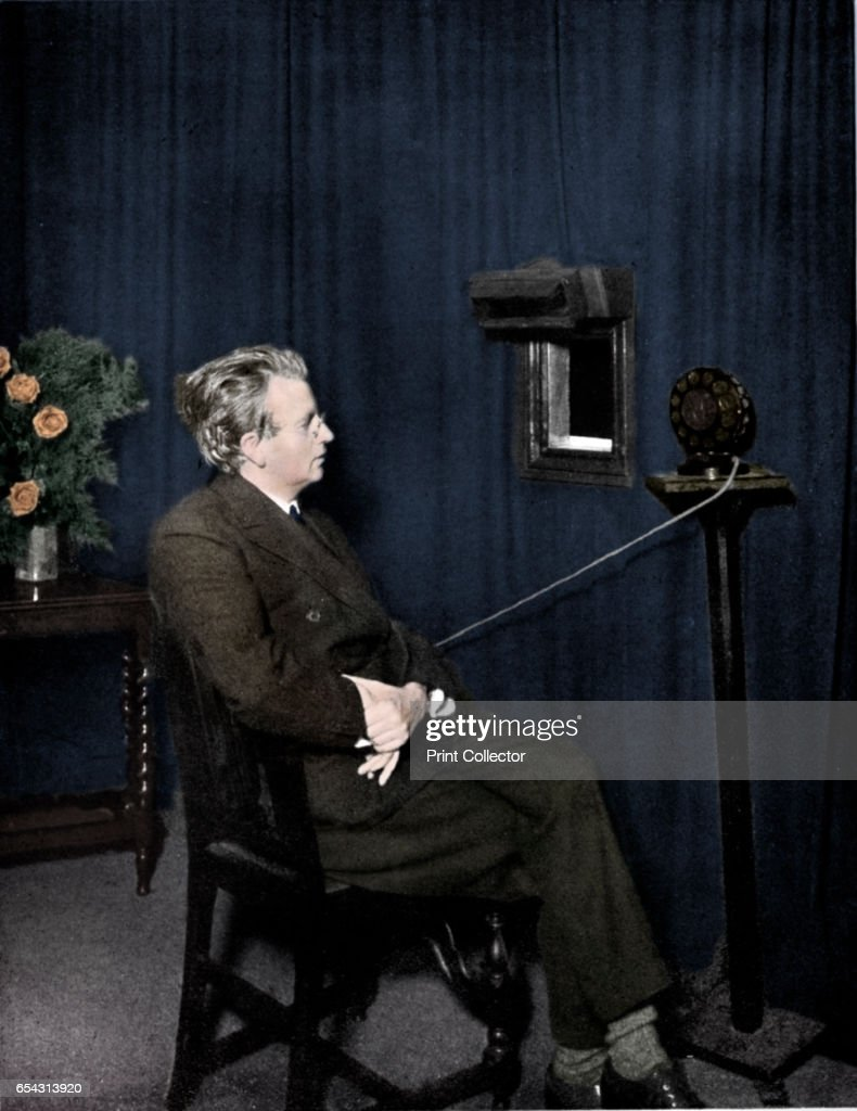 John Logie Baird (1888-1946), Scottish electrical engineer and pioneer of television, 1920s. Baird giving an early television (Seeing by wireless) demonstration. The image is of someone holding two dolls. Baird began experimenting with imaging systems in the early 1920s. In 1924 he transmitted outline images over wires and by 1925 he was able to transmit recognisable human faces. In 1926 he started the worlds first television station, which he named 2TV. (Colorised black and white print). Artist Unknown.