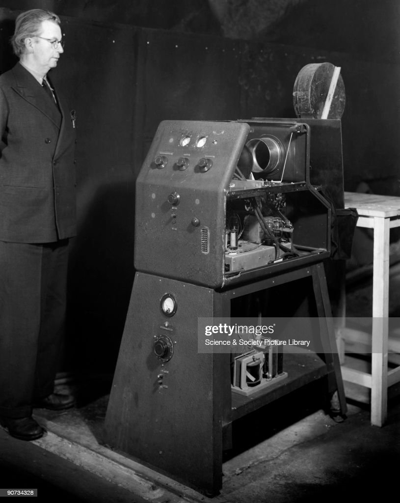 John Logie Baird (1888-1946), television pioneer, c 1942. After a serious illness in 1922, Baird devoted himself to experimentation and developed a crude TV apparatus, able to transmit a picture and receive it over a range of a few feet. The first real demonstration was within two attic rooms in Soho, London, in early 1926, and by 1927 he had managed to transmit pictures by telephone line from London to Glasgow. Baird with his one of his early television projectors, which was used to display BBC outside broadcasts on the cinema screen at the Marble Arch Pavilion in 1938.