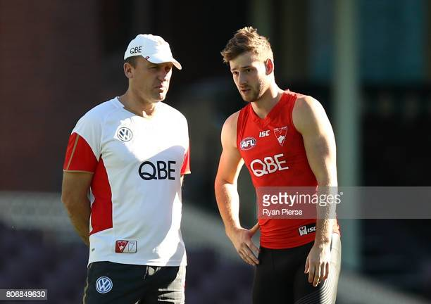 John Longmire coach of the Swans speaks with Alex Johnson of the Swans during a Sydney Swans AFL training session at Sydney Cricket Ground on July 4...