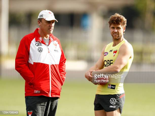 John Longmire coach of the Swans speaks with Dane Rampe of the Swans during a Sydney Swans AFL training session at Lakeside Oval on July 07 2020 in...