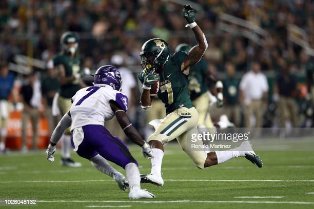 John Lovett of the Baylor Bears runs for a touchdown past Bolu Onifade of the Abilene Christian Wildcats at McLane Stadium on September 1 2018 in...
