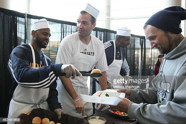 John Lucas III and Michael Sanders Assistant Coach of the Utah Jazz dish out food during the we carewe share Thanksgiving Dinner feeding the homeless...