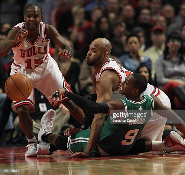 John Lucas III and Taj Gibson of the Chicago Bulls battle for a loose ball with Rajon Rondo of the Boston Celtics at the United Center on February 16...