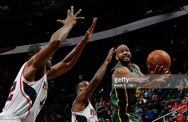 John Lucas III of the Utah Jazz drives against Shelvin Mack and Elton Brand of the Atlanta Hawks at Philips Arena on December 20 2013 in Atlanta...