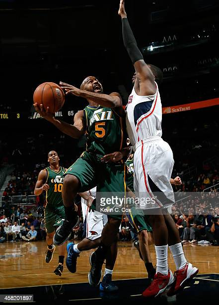 John Lucas III of the Utah Jazz drives against Shelvin Mack of the Atlanta Hawks at Philips Arena on December 20 2013 in Atlanta Georgia NOTE TO USER...