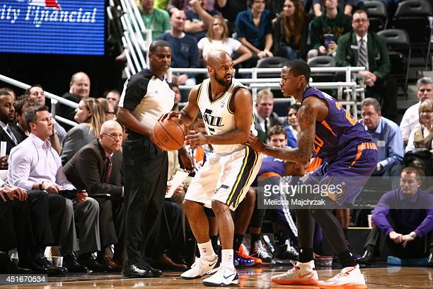 John Lucas III of the Utah Jazz handles the ball against Archie Goodwin of the Phoenix Suns at EnergySolutions Arena on February 26, 2014 in Salt...