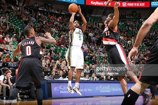 John Lucas III of the Utah Jazz shoots against Damian Lillard and LaMarcus Aldridge of the Portland Trail Blazers at Energy Solutions Arena on...