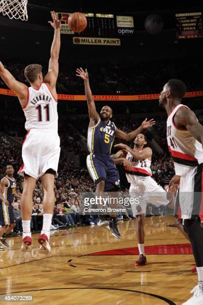 John Lucas III of the Utah Jazz shoots against Meyers Leonard of the Portland Trail Blazers on December 6 2013 at the Moda Center Arena in Portland...