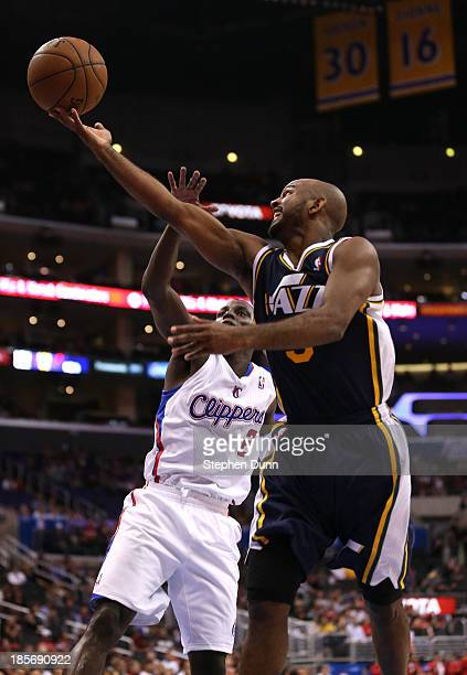 John Lucas III of the Utah Jazz shoots over Darren Collison of the Los Angeles Clippers at Staples Center on October 23, 2013 in Los Angeles,...