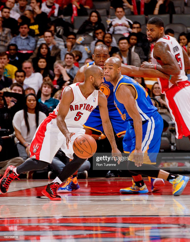 John Lucas #5 of the Toronto Raptors drives against Jarrett Jack #2 of the Golden State Warriors on January 28, 2013 at the Air Canada Centre in Toronto, Ontario, Canada.